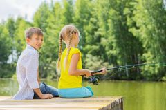 Summer leisure. Rear view of two children sitting at bank and fishing Royalty Free Stock Photos