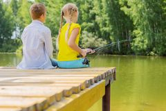 Summer leisure. Rear view of two children sitting at bank and fishing Royalty Free Stock Images