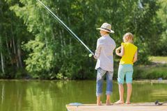 Summer leisure. Rear view of two children standing at bank and fishing Stock Photos