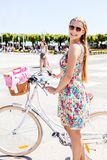Summer leisure time. Woman in summer dress with bicycle, outdoor. Active leisure time royalty free stock photo