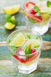 Summer lemonade or cocktail with lime, ice, strawberry and green mint in glass on rustic table, mojito Royalty Free Stock Image
