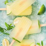 Summer lemonade popsicles with lime and chipped ice, square crop. Summer refreshing lemonade popsicles with lime and mint with chipped ice over blue background stock images