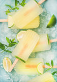 Summer lemonade popsicles with lime and chipped ice, top view. Summer refreshing lemonade popsicles with lime and mint with chipped ice over blue background, top Stock Image