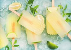 Summer lemonade popsicles with lime and chipped ice, top view. Summer refreshing lemonade popsicles with lime and mint with chipped ice over blue background, top Royalty Free Stock Photos