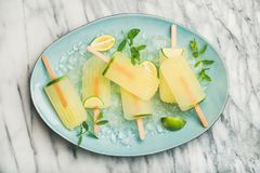Summer lemonade popsicles with lime, mint leaves and chipped ice. Summer refreshing lemonade popsicles with lime, mint leaves and chipped ice on blue plate over Stock Image