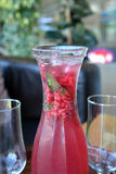 Summer lemonade with raspberry and leaves mint in a glass jug. Fresh raspberry lemonade with mint in a glass jug Stock Photo