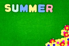 Summer lettering on a green background with flowers and copy space royalty free stock photo