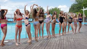 Summer life of youth on weekend, smiling girlfriends in swimsuit have fun near poolside, crowd of woman on resort,
