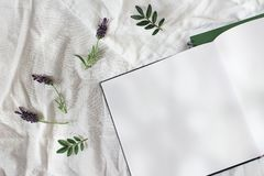 Summer lifestyle floral composition. Open blank diary, sketch book mockup scene with lavender flowers and green leaves. Bed in sunny day. White linen royalty free stock photos