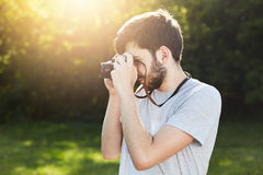 Summer lifestyle image of bearded man making photos with retro camera standing sideways photographing someone. Young photographer Stock Photos
