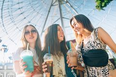 Summer lifestyle portrait multiracial women enjoy nice day, holding glasses of milkshakes. Happy friends inin front of. Happy friends in the park on a sunny day royalty free stock images