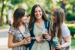 Summer lifestyle portrait multiracial women enjoy nice day, holding glasses of milkshakes. Happy friends in the park on stock photography
