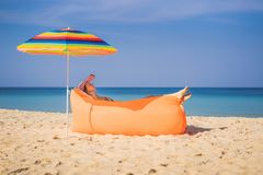 Summer lifestyle portrait of pretty girl sitting on the orange inflatable sofa on the beach of tropical island. Relaxing stock images