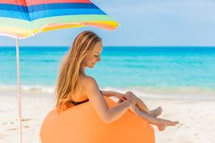 Summer lifestyle portrait of pretty girl sitting on the orange inflatable sofa on the beach of tropical island. Relaxing. And enjoying life on air bed stock images