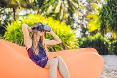Summer lifestyle portrait of pretty girl sitting on the orange inflatable sofa and uses virtual reality headset on the royalty free stock image