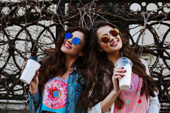 Summer lifestyle portrait of two hipster stylish women with fit sexy body, wearing denim outfit and vintage sunglasses Royalty Free Stock Photography