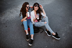 Summer lifestyle portrait of two hipster stylish women with fit sexy body, wearing denim outfit and vintage sunglasses Royalty Free Stock Images