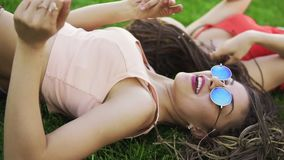 Summer lifestyle portrait of two hipster women laying on the grass, enjoying nice day, wearing bright sunglasses. Best. Trendy hipster girls relaxing on the stock footage