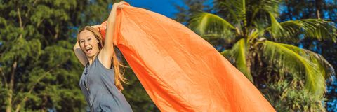 Summer lifestyle portrait of woman inflates an inflatable orange sofa on the beach of tropical island. Relaxing and royalty free stock photos