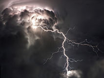 Lightning bolts and storm clouds. Towering summer monsoon storm clouds with large branched lightning stock photography