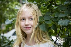 In summer, the blue-eyed blonde girl is a teenager in the foliag. In the summer in the lilac foliage there is a blue-eyed blond girl, a teenager Stock Photography