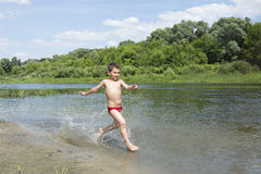 In summer, the little boy runs along the river bank. Stock Image