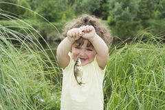 In the summer of little curly girl in awe of carp caught. Stock Image