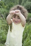 In the summer of little curly girl in awe of carp caught. Royalty Free Stock Photography