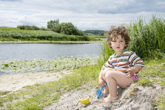 Summer little curly girl playing with a shovel on the riverbank. Royalty Free Stock Image
