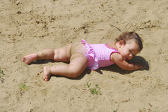 Summer little funny, dirty girl sunning at the lake in the sand Stock Photo
