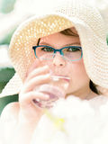 Summer little girl in straw hat drinking water outdoor portrait. Royalty Free Stock Photography