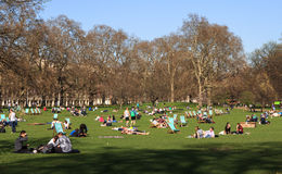 Summer London Park. People relaxing in a London Park on  Striped Deck Chairs Stock Photos