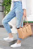 Summer look. White shirt, jeans, brown leather bag and sneakers shoes Stock Photo