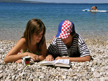 Summer love. Germany girl and Croatian boy reading dictionary on the Adriatic sea (Croatia-Dalmatia Royalty Free Stock Photography