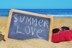 Summer love. A blackboard with sentence summer love written on it, at towel and sunglasses on the beach Royalty Free Stock Image