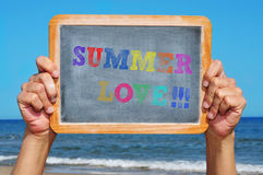 Summer love. Someone holding a blackboard with the sentence summer love written on it on the beach Stock Photos