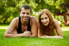 Summer love. Happy guy and the girl on a grass Royalty Free Stock Photos