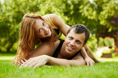 Summer love. Happy guy and the girl on a grass Stock Images