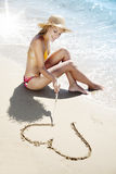 Summer love. Young female in bikini drawing love-heart in the sand Stock Images