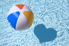 Summer love. Beach Ball on the swimming Pool with heart shaped shadow Royalty Free Stock Photography