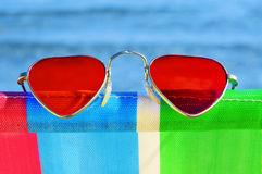 Summer love on the beach. Heart-shaped sunglasses on a colorful deckchair on the beach Stock Images