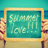 Summer love. Picture of someone on the beach holding a blackboard with the sentence summer love written on it, with a retro effect Royalty Free Stock Photo