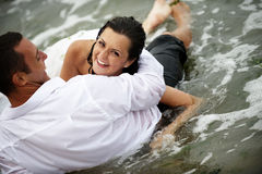 Summer lovers (couple portrait). Beautiful happy couple posing in the sea stock photo