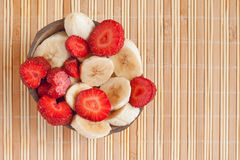 Summer lunch: cut bananas and strawberries Stock Images