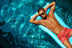 Summer Man Body Care. Beautiful Male Relaxing In Pool. Summer Man Body Sun Skin Care. Beautiful Model With Sexy Body In Swimwear Tanning, Floating On Mattress In Stock Photos