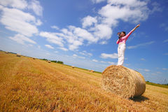 Summer management. Girl speaking through megaphone and pointing in field of hay bales Royalty Free Stock Photo