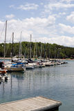 Summer at the marina. A foreground pier with a lineup of sail boats and sky in the background Stock Images
