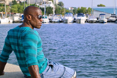 Summer marine scene with a handsome black man relaxing and enjoying the summer. Stock Photography