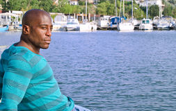 Summer marine scene with a handsome black man relaxing and enjoying the summer. Stock Photos