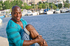 Summer marine scene with a handsome black man relaxing and enjoying the summer. Royalty Free Stock Photo